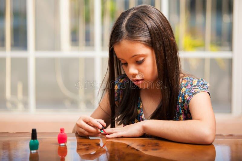 Śliczna mała dziewczynka używa gwoździa połysk zdjęcie stock