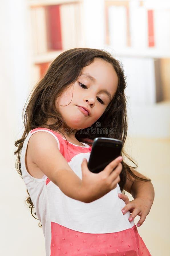 Śliczna mała dziewczynka używa telefon komórkowego bierze selfie obraz royalty free