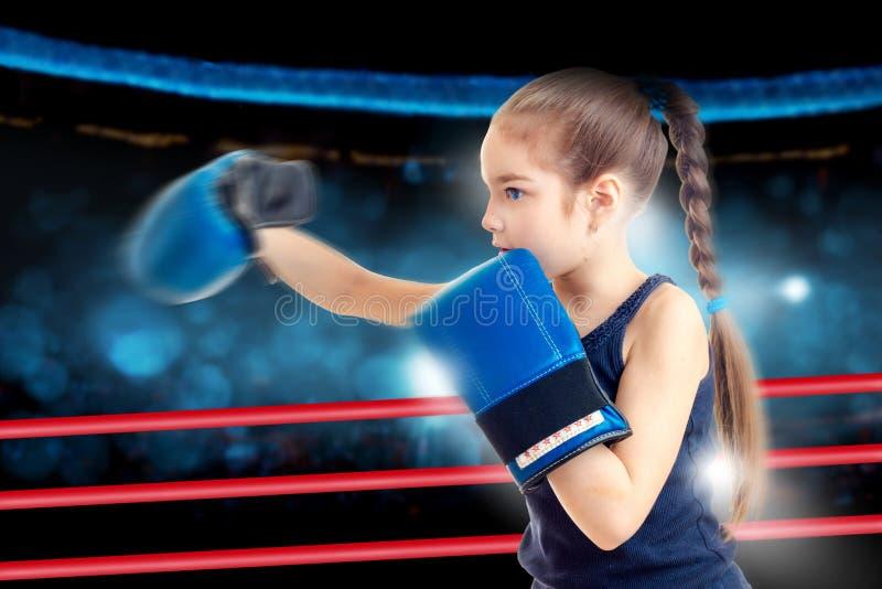 Śliczna mała dziewczynka uderza pięścią w bokserskich rękawiczkach zdjęcie stock