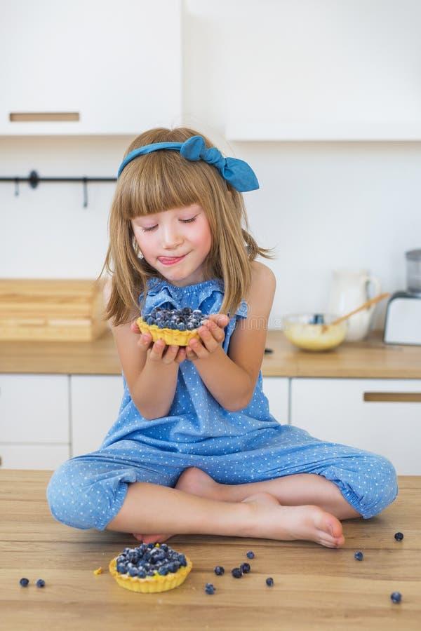 Śliczna mała dziewczynka w błękit sukni siedzi na, liże jej wargi i stole z tortem i spojrzeniach na nim zdjęcie royalty free