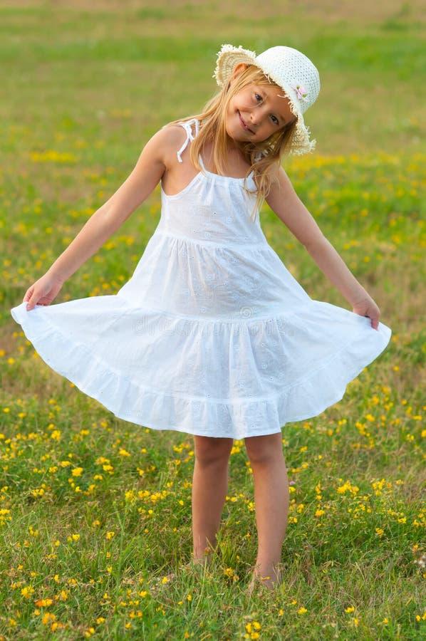 Śliczna mała dziewczynka w biel smokingowym i kapeluszowym odprowadzeniu fotografia stock