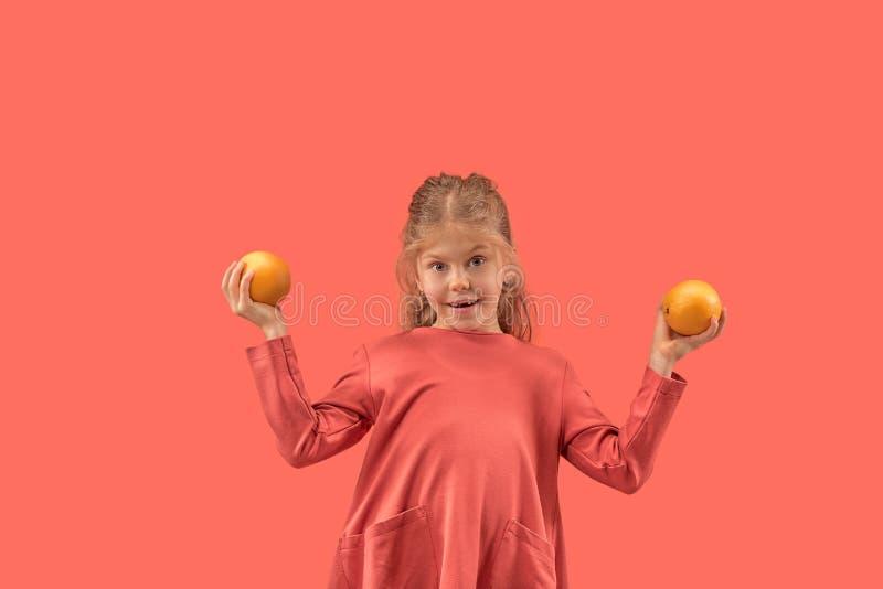Śliczna mała dziewczynka w koral sukni z długie włosy ono uśmiecha się kamera zdjęcia royalty free