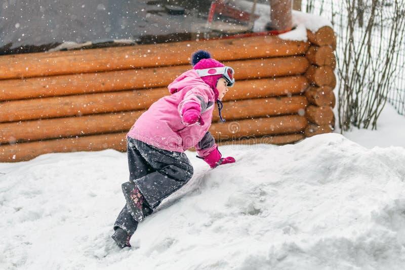 Śliczna mała dziewczynka w menchiach bawi się kostium ma zabawę bawić się outdoors podczas opad śniegu w zimie Dziecko zimy sezon zdjęcie stock