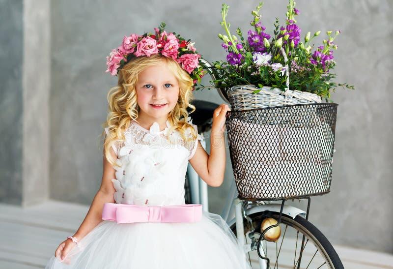 Śliczna mała dziewczynka w pięknej luksusowej biel sukni w wianku kwiaty na ona kierownicza stać w studiu obok roweru obrazy royalty free
