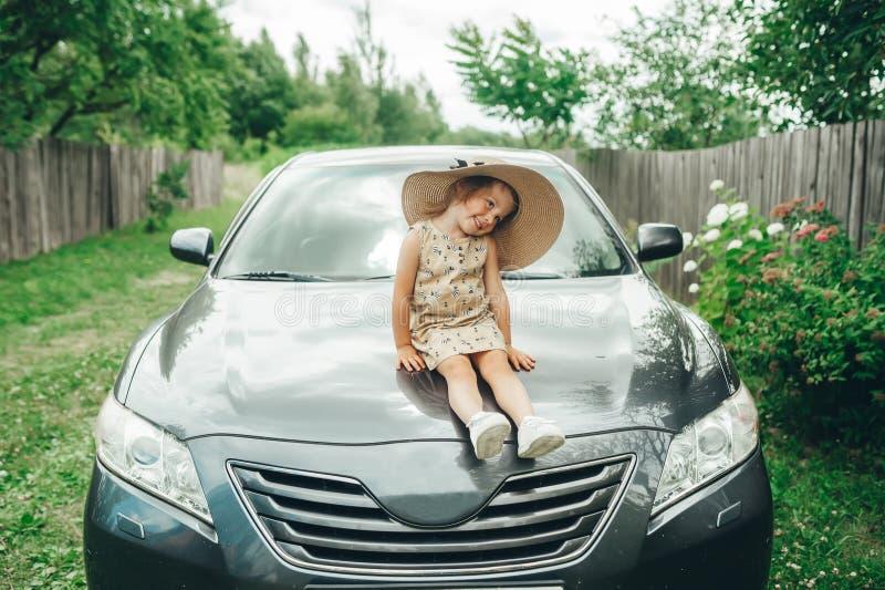 Śliczna mała dziewczynka w słomianego kapeluszu obsiadaniu na samochodowym cowl w podwórko obrazy royalty free