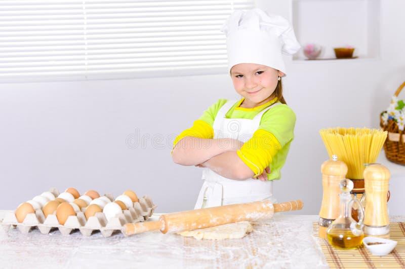 Śliczna mała dziewczynka w szefa kuchni ` s pieczenia kapeluszowym torcie w kuchni fotografia stock