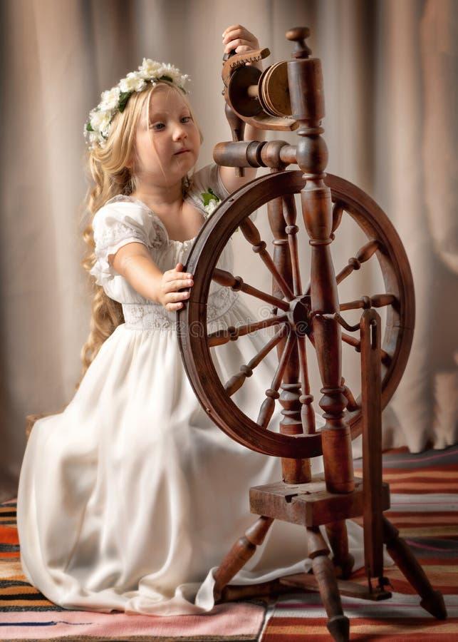 Śliczna mała dziewczynka wyplatał wełnę z płodozmiennym kołem zdjęcie stock