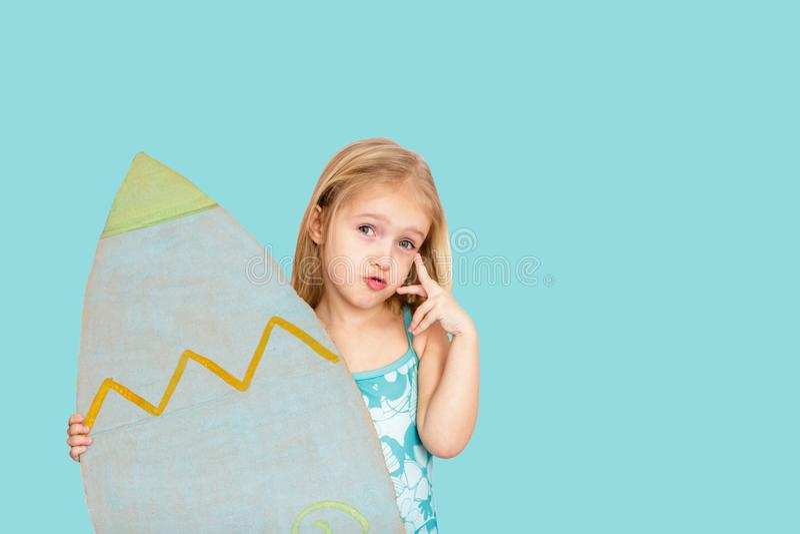 Śliczna mała dziewczynka z blondynka włosy mienia surfboard na błękitnym tle miejsce tekst zdjęcia stock