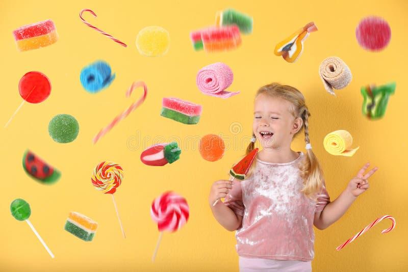 Śliczna mała dziewczynka z cukierkiem na tle Przestrzeń dla teksta fotografia royalty free