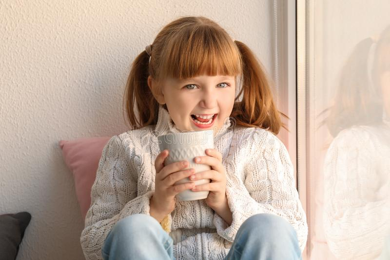 Śliczna mała dziewczynka z filiżanką gorący kakaowy napój blisko okno obraz royalty free