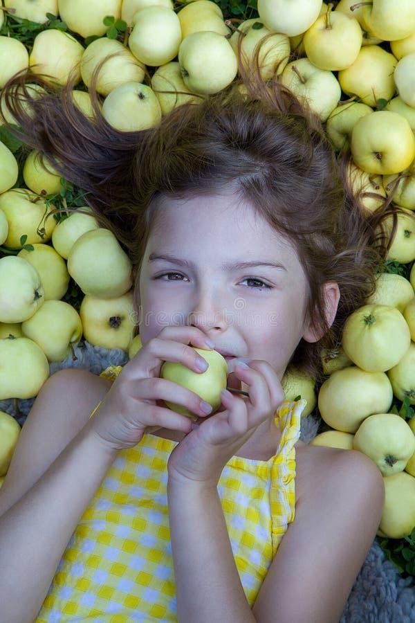 Śliczna mała dziewczynka z jabłkami na naturalnym tle fotografia royalty free