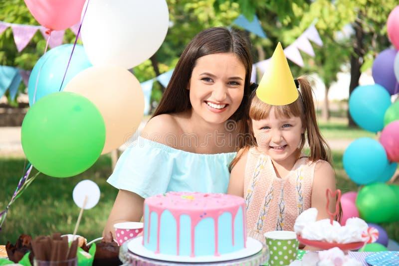 Śliczna mała dziewczynka z jej matką przy przyjęciem urodzinowym outdoors obraz stock