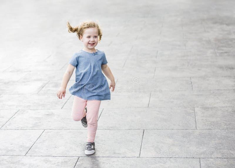 Śliczna mała dziewczynka z kędzierzawego włosy śmiać się outdoors i bieg kosmos kopii fotografia stock