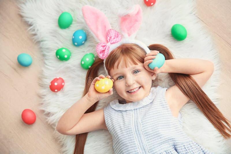 Śliczna mała dziewczynka z królików ucho i kolorowymi Wielkanocnymi jajkami zdjęcie stock