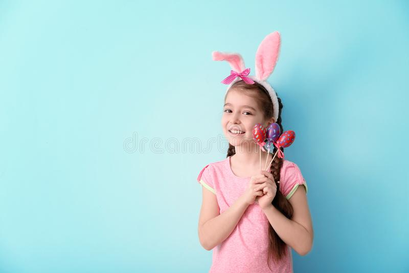 Śliczna mała dziewczynka z królików ucho i Wielkanocnymi jajkami na koloru tle zdjęcia stock