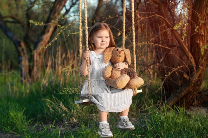 Śliczna mała dziewczynka z królika zabawkarski bawić się na huśtawce obrazy royalty free