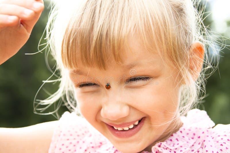 Dziewczyna z ladybird na jej nosie zdjęcia royalty free