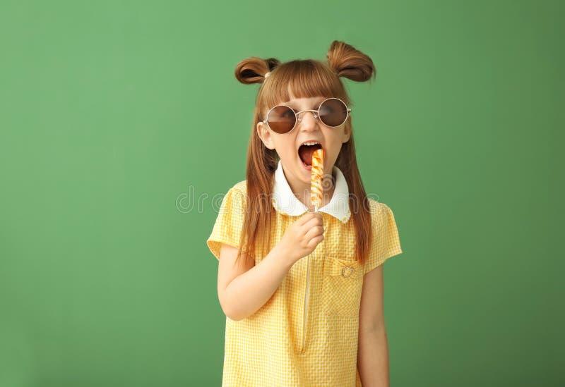 Śliczna mała dziewczynka z lizakiem na koloru tle zdjęcia royalty free