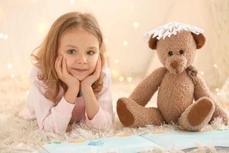 Śliczna mała dziewczynka z miś czytelniczą książką obrazy royalty free