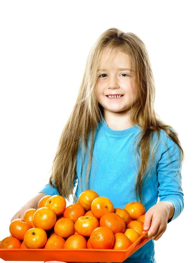 Śliczna mała dziewczynka z pełną tacą mandarynki zdjęcia stock