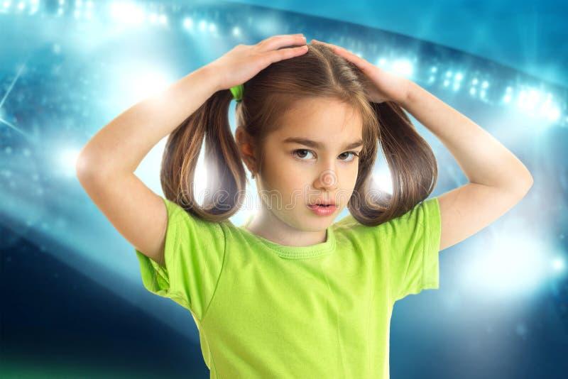 Śliczna mała dziewczynka z pigtails w zielonej futbolowej koszula zdjęcia stock