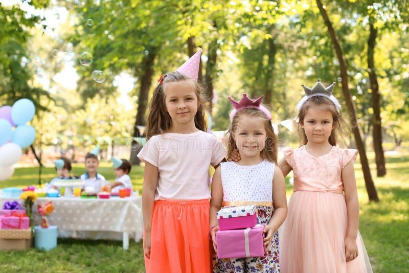 Śliczna mała dziewczynka z prezentów pudełkami i jej przyjaciółmi przy przyjęciem urodzinowym outdoors obrazy stock