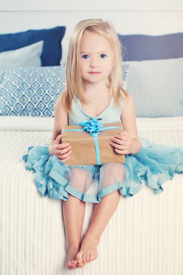 Śliczna mała dziewczynka z prezenta pudełkiem szczęśliwy dziecko dom zdjęcia stock