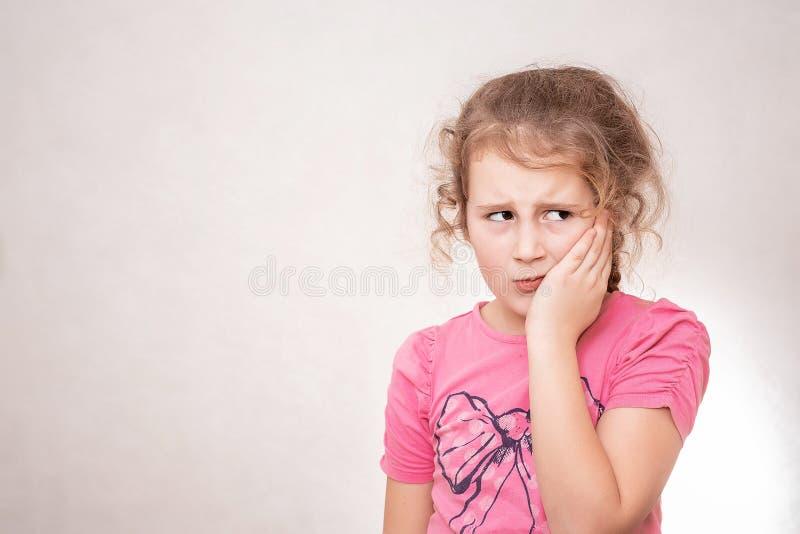 Śliczna mała dziewczynka z Stomatologicznym problemem, mieć surowego ból i prawie płaczący Sta? nad szarym t?em fotografia stock