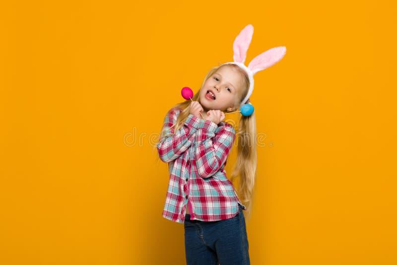 Śliczna mała dziewczynka z Wielkanocnego królika ucho trzyma kolorowych jajka obrazy royalty free