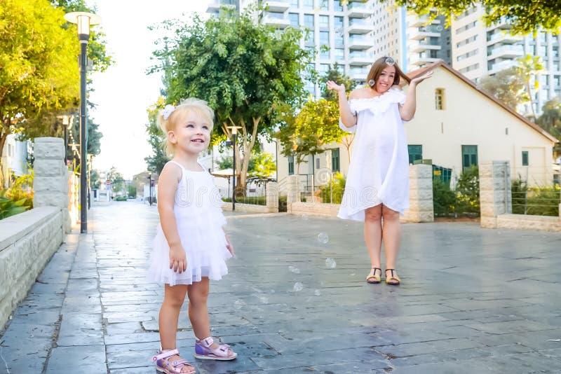 Śliczna mała emocjonalna blondy berbeć dziewczyna w sukni z ciężarny macierzysty bawić się, łapie mydlanych bąble podczas spaceru zdjęcie stock