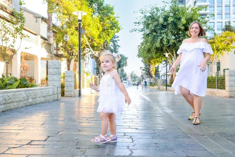 Śliczna mała emocjonalna blondy berbeć dziewczyna w sukni z ciężarny macierzysty bawić się, łapie mydlanych bąble podczas spaceru zdjęcia royalty free