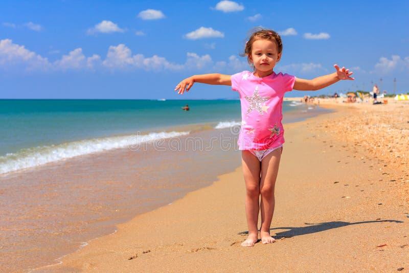 Śliczna mała Kaukaska dziewczyny pozycja na piaskowatej plaży przy lato nadmorski na słonecznym dniu na niebieskim niebie i denny zdjęcie stock