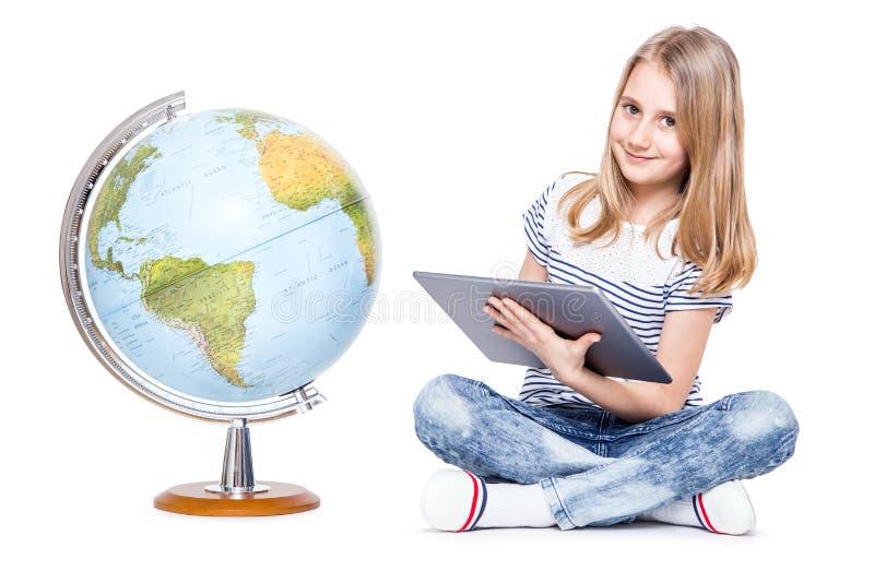 śliczna mała młoda dziewczyna z pastylką i kulą ziemską Uczennica używa nowożytną technologię w nauczanie geografii fotografia royalty free