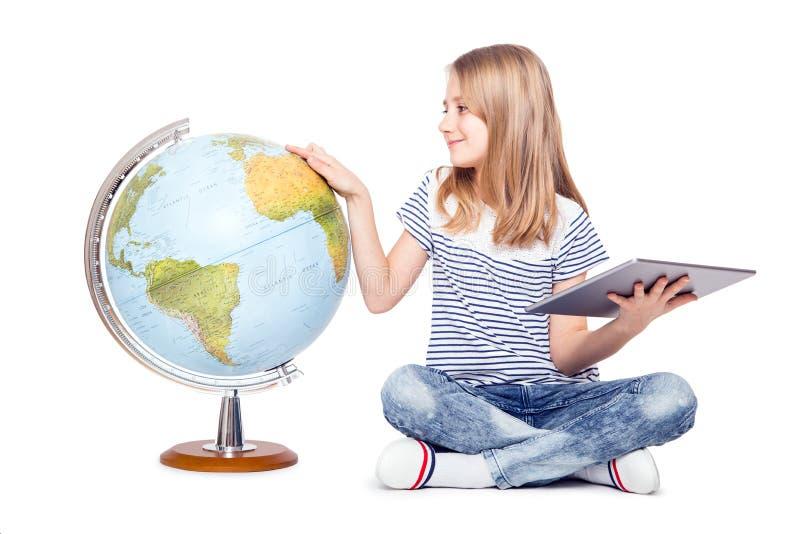 śliczna mała młoda dziewczyna z pastylką i kulą ziemską Uczennica używa nowożytną technologię w nauczanie geografii zdjęcie royalty free