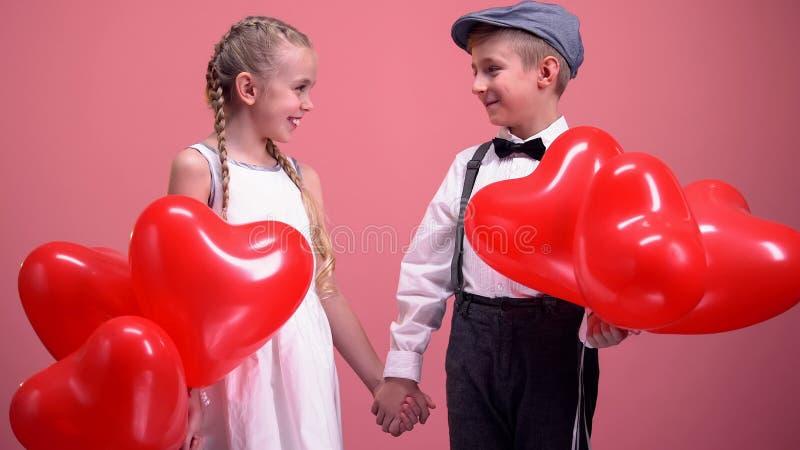 Śliczna mała para trzyma ręki i ono uśmiecha się z balonami, dzieciaki na miłości datuje zdjęcia royalty free