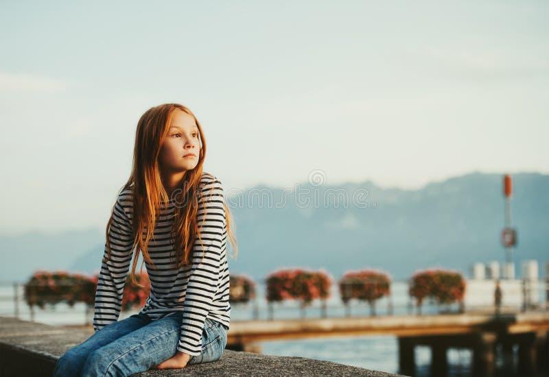 Śliczna mała redheaded dziewczyna odpoczywa jeziornym Genewa przy zmierzchem zdjęcie royalty free