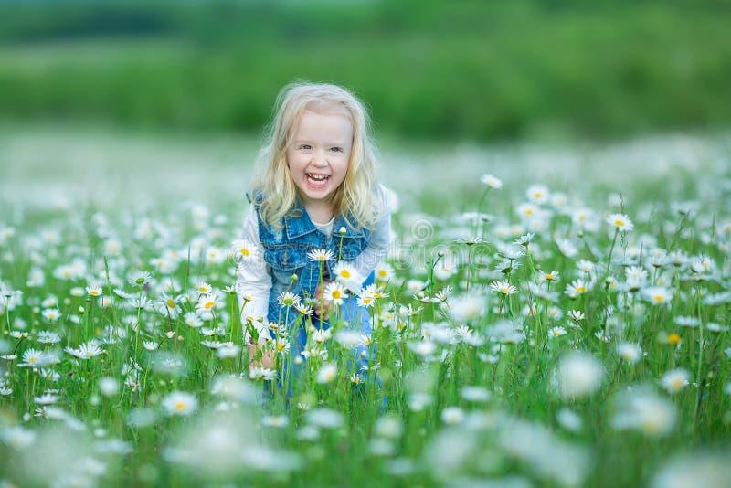 Śliczna mała uśmiechnięta dziewczynka w chamomile pola Małym blond dziecku z wiankiem na głowie w chamomiles jest ubranym cajgi i fotografia stock
