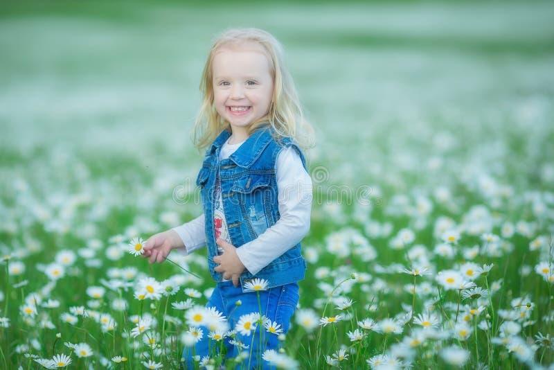 Śliczna mała uśmiechnięta dziewczynka w chamomile pola Małym blond dziecku z wiankiem na głowie w chamomiles jest ubranym cajgi i zdjęcie stock