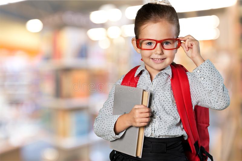 Śliczna mała uczennica w szkłach na bibliotece obraz royalty free