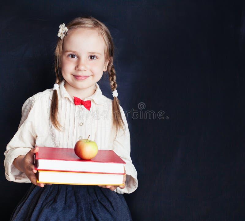 Śliczna mała uczennica z czerwonym jabłkiem i książkami zdjęcie royalty free