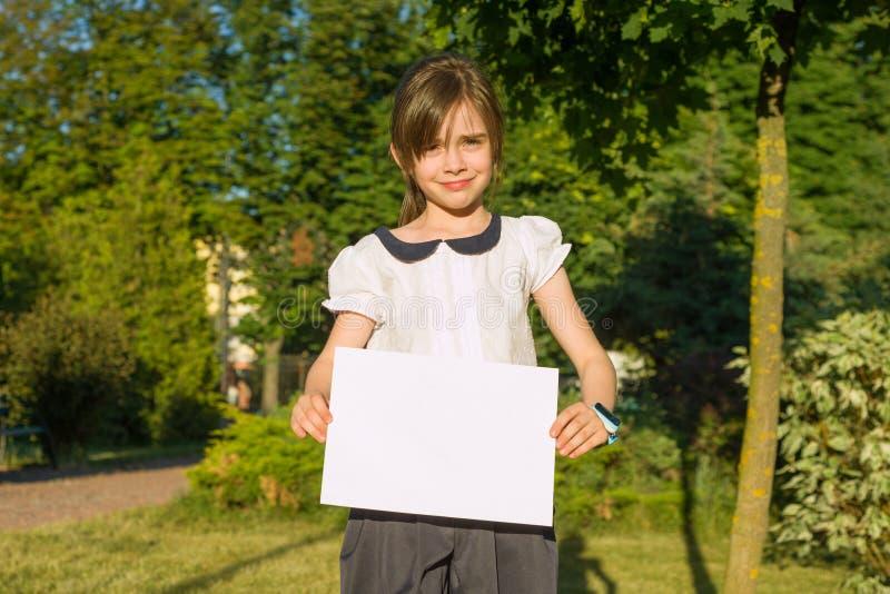 Śliczna mała uczennica z pustym prześcieradłem papier dla reklamować na natury tle obrazy stock