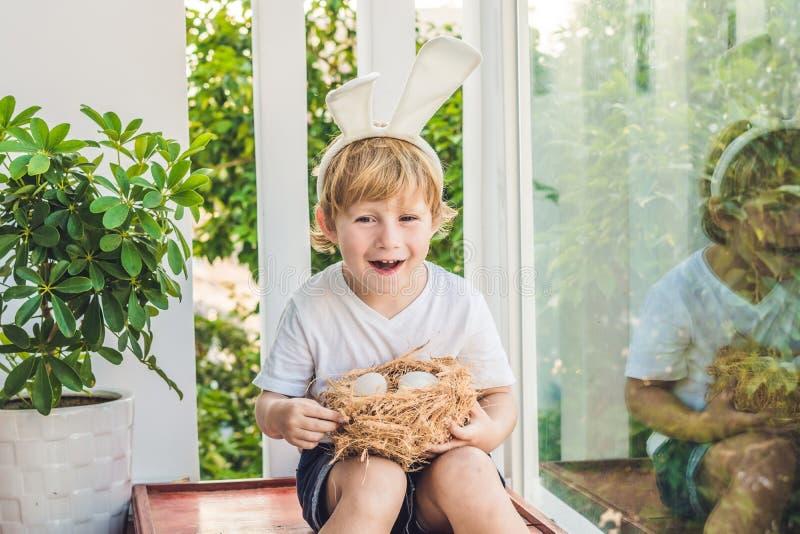 Śliczna małe dziecko chłopiec jest ubranym królików ucho na Wielkanocnym dniu Chłopiec mienia gniazdeczko z jajkami zdjęcie stock