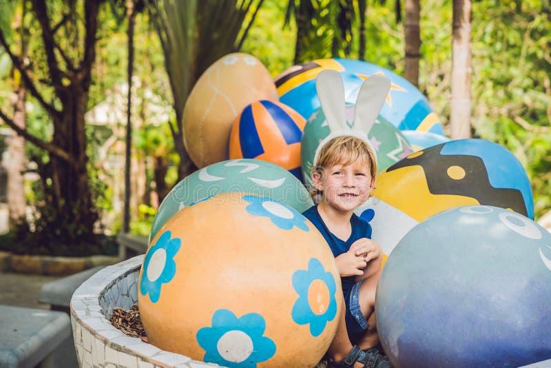 Śliczna małe dziecko chłopiec z królików ucho ma zabawę z tradycyjnymi Wielkanocnymi jajkami tropi, outdoors r Berbeć fi obraz stock