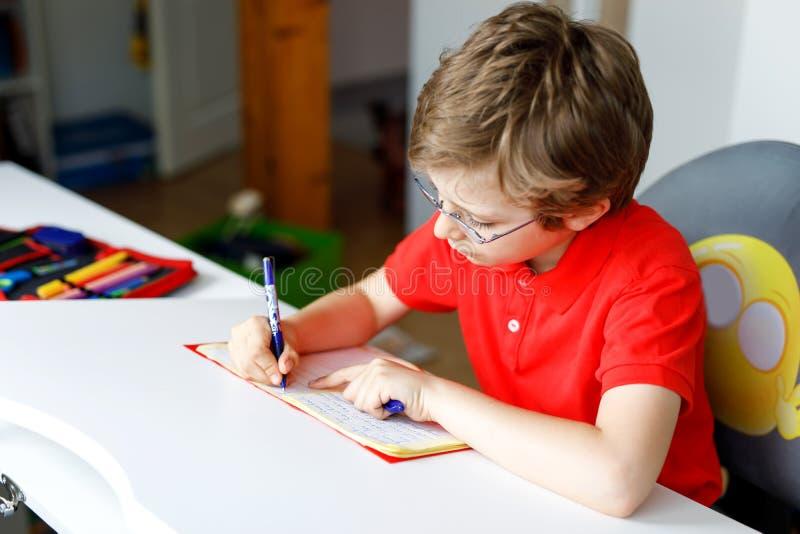 Śliczna małe dziecko chłopiec z szkłami robi pracie domowej w domu, pisze listach z kolorowymi piórami obraz stock