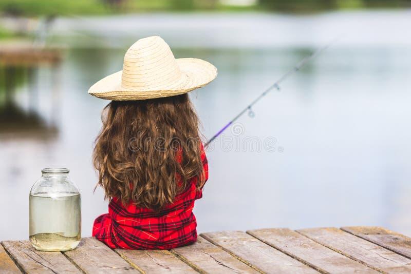 Śliczna małe dziecko dziewczyna w gumowych butach i słomianego kapeluszu połów od drewnianego mola blisko szklanego słoju i małej obraz royalty free
