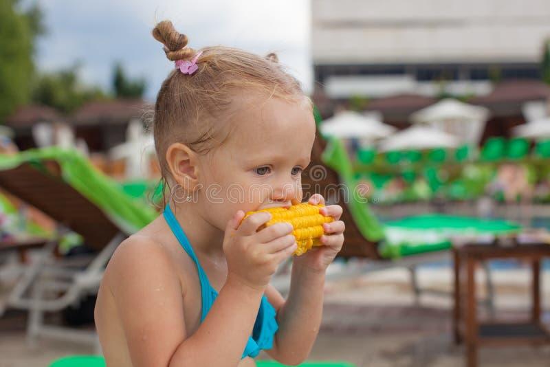 Śliczna małej dziewczynki łasowania kukurudza przy basenem dalej obrazy royalty free