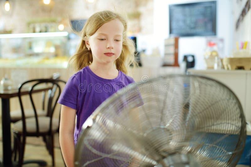 Śliczna małej dziewczynki pozycja przed fan na gorącym letnim dniu Dziecko cieszy się chłodno wiatr w lato sezonie zdjęcia royalty free