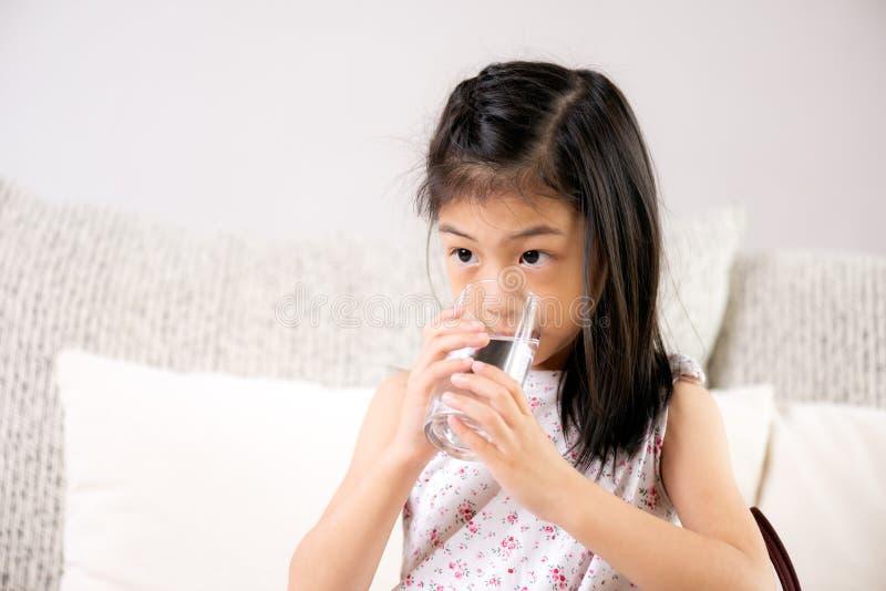 Śliczna małej dziewczynki woda pitna na kanapie w domu tło zamazywał opieki pojęcia twarzy zdrowie maski pigułkę ochronną obrazy royalty free