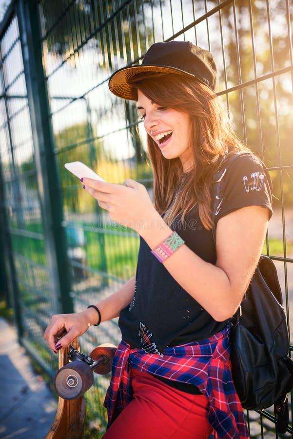 Śliczna miastowa dziewczyna w skatepark z deskorolka używać mądrze telefon obrazy royalty free