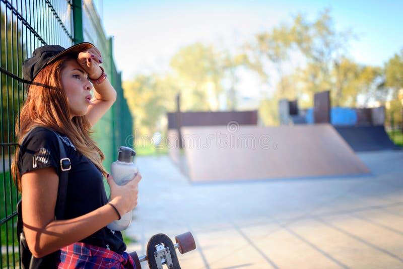 Śliczna miastowa dziewczyna z deskorolka wodą pitną na gorącym dniu zdjęcie royalty free